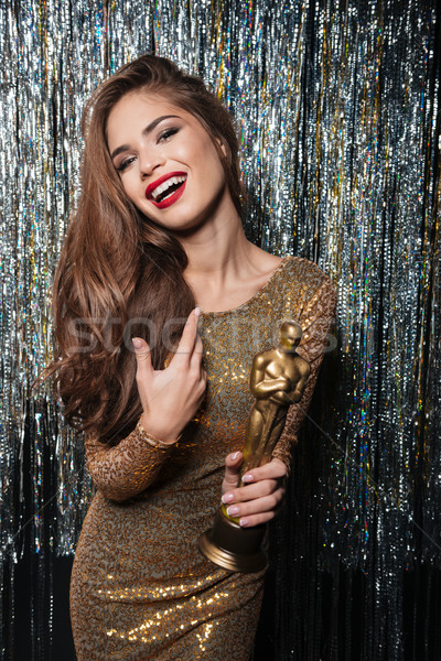 Happy young woman in evening dress smiling and holding award Stock photo © deandrobot