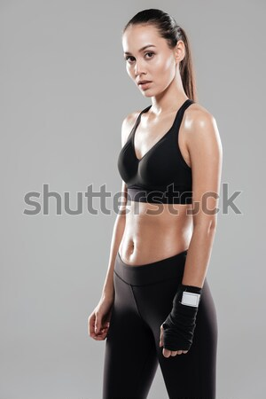Beautiful young woman athlete with boxing wraps on her hand Stock photo © deandrobot