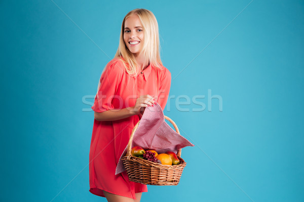 Beautiful blonde woman with a wicker basket full of fruits Stock photo © deandrobot
