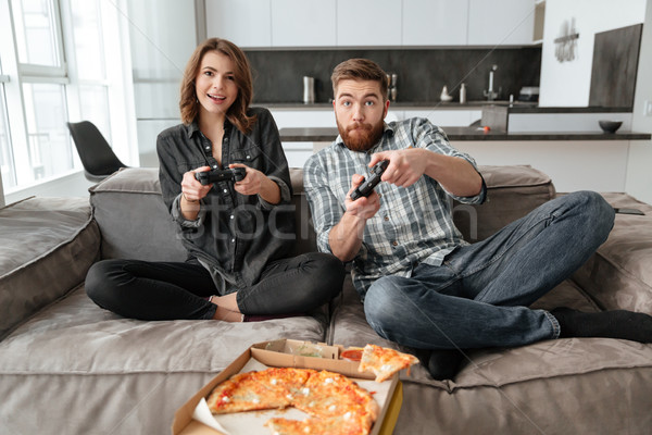Loving couple eating pizza and playing games with console. Stock photo © deandrobot