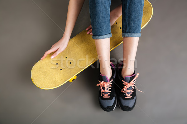 Women legs in sneakers sitting on the floor with skateboard Stock photo © deandrobot