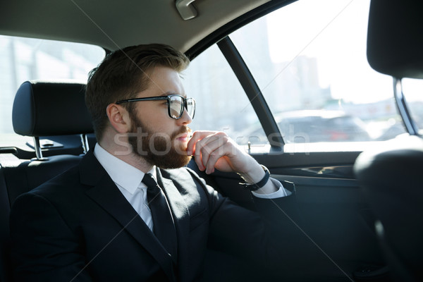 Man in eyeglasses sitting at the back seat of car Stock photo © deandrobot
