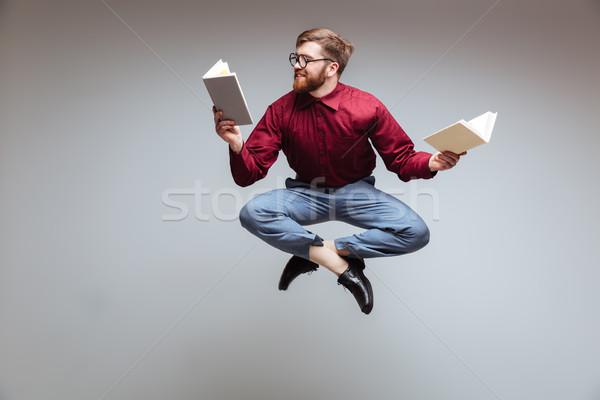 Männlich nerd springen Lesung isoliert grau Stock foto © deandrobot