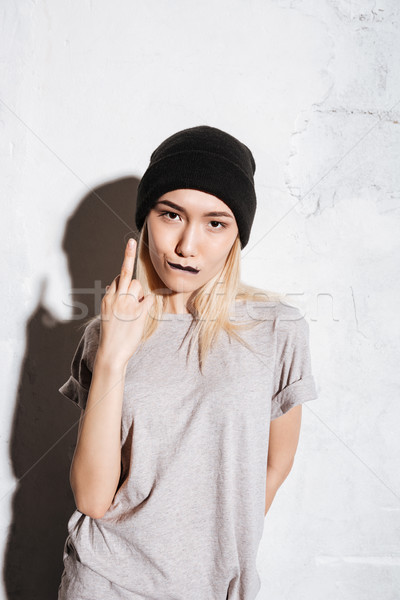 Bad rude young woman in black hat showing middle finger Stock photo © deandrobot