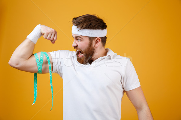Happy young fitness man measuring his biceps Stock photo © deandrobot