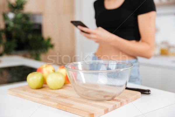 Cropped image of woman in kitchen using phone Stock photo © deandrobot