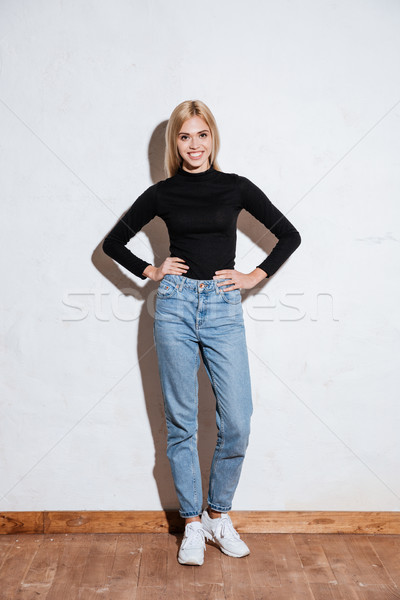 Stock photo: Woman standing with hands on hips and looking at camera