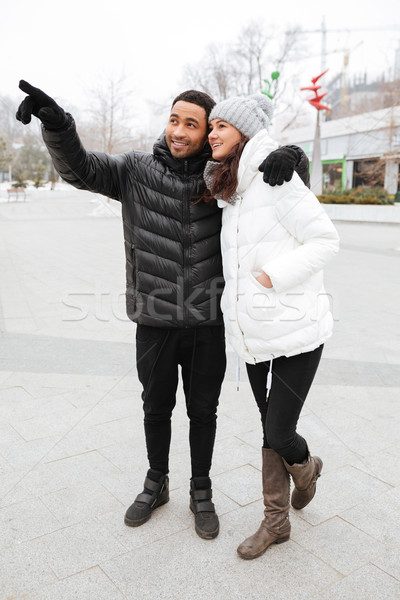 Happy couple standing and pointing away at winter park Stock photo © deandrobot