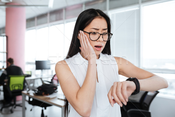 Amazed shocked businesswoman looking at wristwatch in office Stock photo © deandrobot