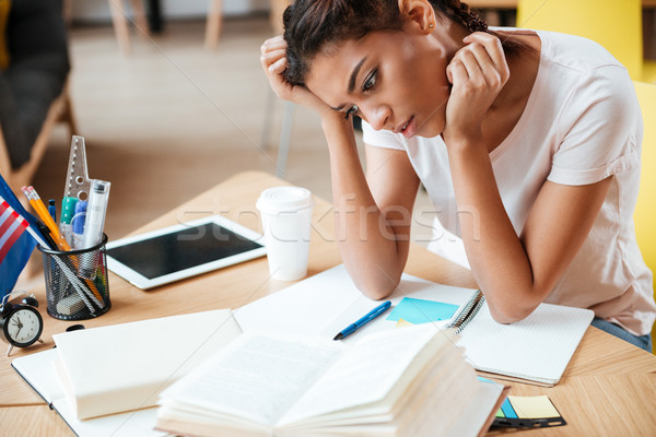Thoughtful African woman in library Stock photo © deandrobot