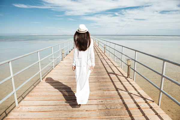Back view of woman in white clothes walking on pier Stock photo © deandrobot