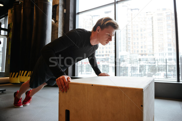 Side view of Young Athletic man push-ups on box Stock photo © deandrobot