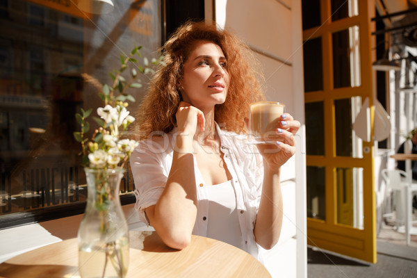 Stock photo: Attractive young woman with curly hair sitting at the table