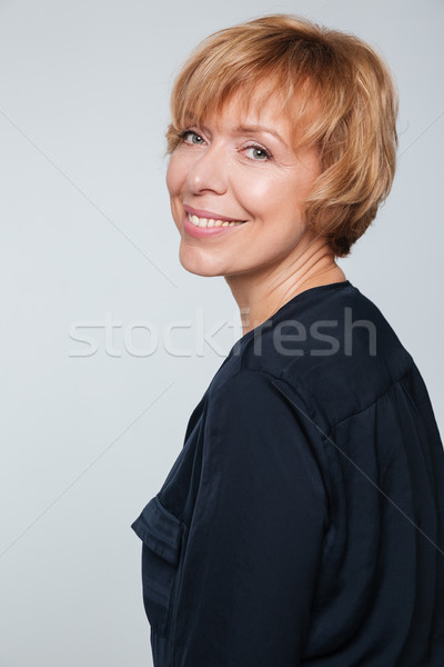 Vertical image of smiling elderly woman standing sideways Stock photo © deandrobot