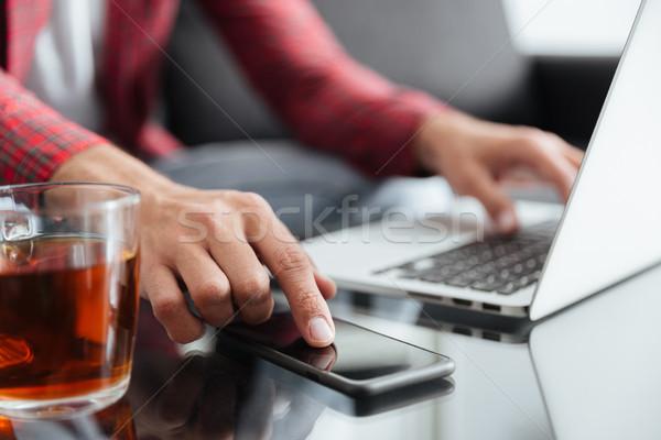 Close up shot of man using gadgets Stock photo © deandrobot