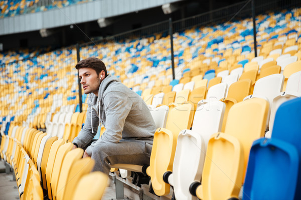 Serious young sports man at the stadium outdoors listening music Stock photo © deandrobot