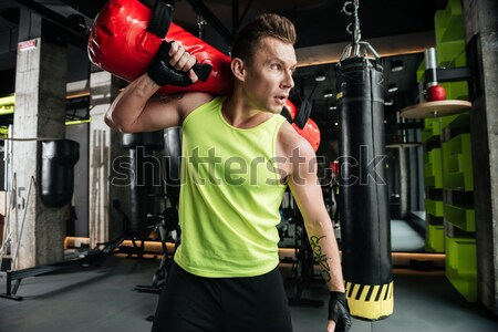 Concentrated sportsman holding weight ball while standing at the gym Stock photo © deandrobot