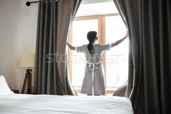 Female chambermaid opening window curtains in the hotel room Stock photo © deandrobot