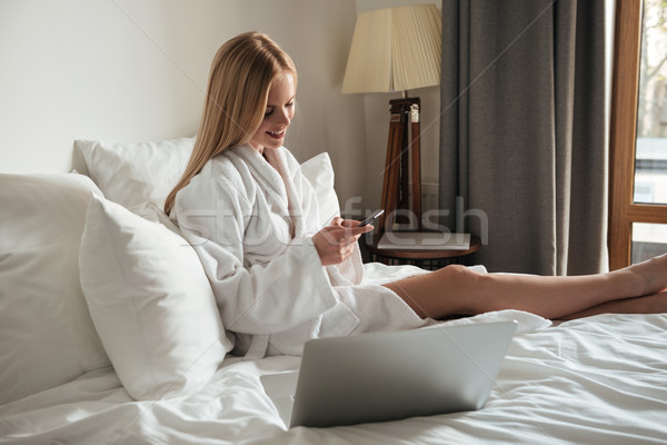 Beautiful young woman in bathrobe sitting on bed Stock photo © deandrobot