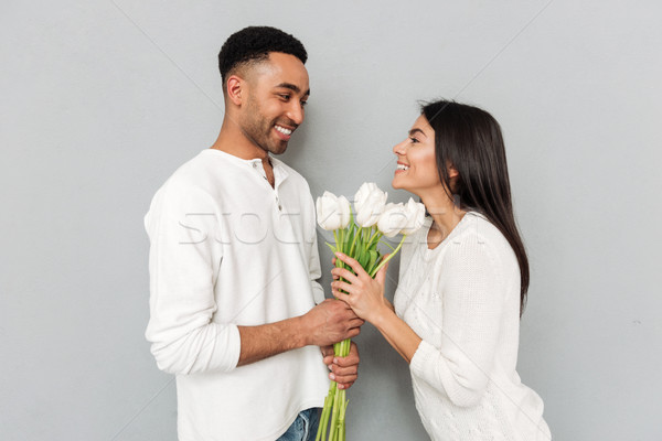 Cheerful young loving couple standing over grey wall Stock photo © deandrobot