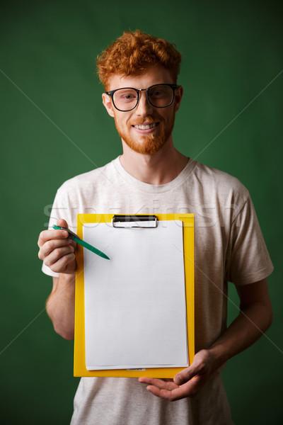 Smart readhead bearded man in white tshirt showing folder with c Stock photo © deandrobot