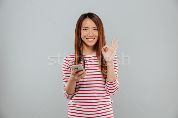 Alegre jovem asiático mulher telefone Foto stock © deandrobot