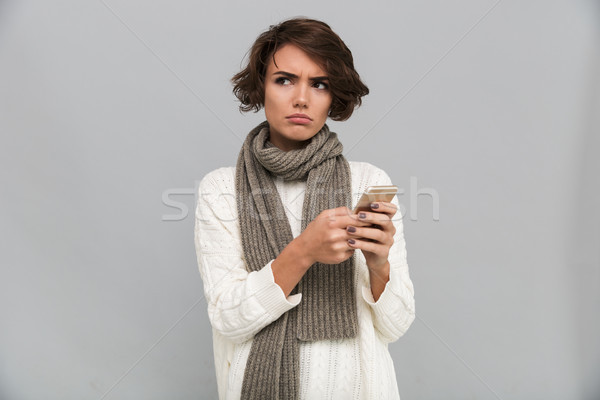 Displeased young lady wearing scarf chatting by mobile phone. Stock photo © deandrobot