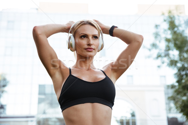 Concentrated strong young sports woman listening music Stock photo © deandrobot
