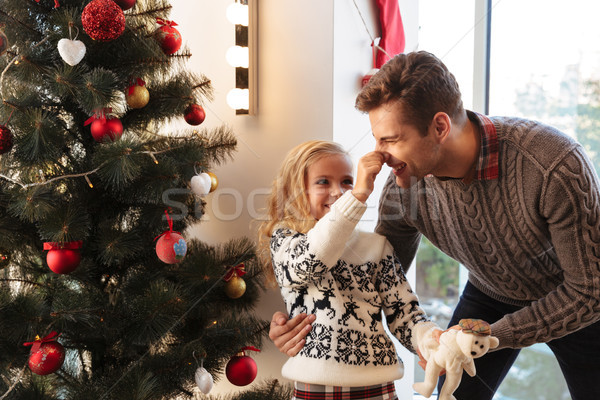 Little girl in having fun with her father while pinch his nose a Stock photo © deandrobot