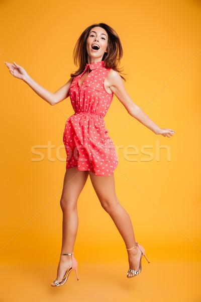 Full length portrait of charming brunette woman in red dress hav Stock photo © deandrobot