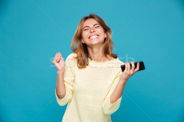 Image of Happy woman in sweater holding smartphone and rejoice Stock photo © deandrobot