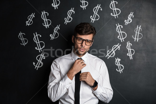 Confident yong man inglasses and white shirt straightens his tie Stock photo © deandrobot