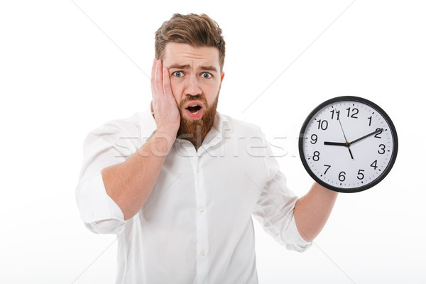 Worried bearded man in business clothes holding clock Stock photo © deandrobot