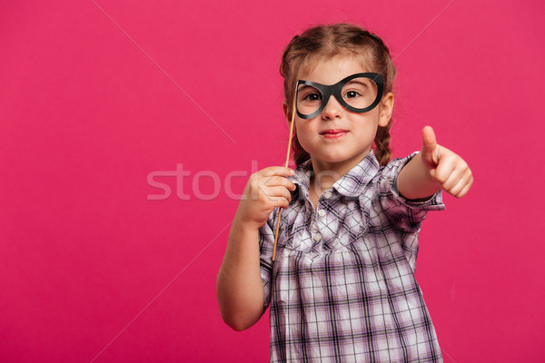 Cheerful little girl child holding fake glasses showing thumbs up. Stock photo © deandrobot