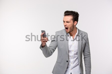 Portrait of young businessman drinking takeaway coffee while hav Stock photo © deandrobot
