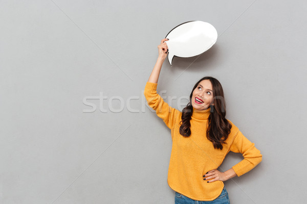 Happy brunette woman in sweater with arm on hip Stock photo © deandrobot