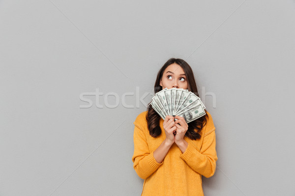 Mystery brunette woman in sweater hiding behind the money Stock photo © deandrobot