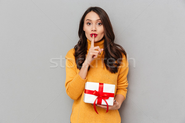 Pretty brunette woman holding gift box and showing silence gesture Stock photo © deandrobot