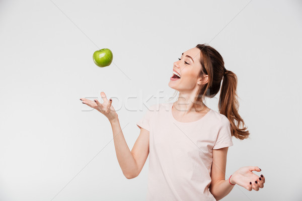 Portrait of a smiling girl throwing apple in the air Stock photo © deandrobot