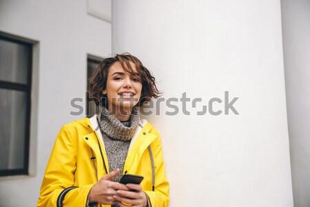 Mosolyog fiatal nő esőkabát kép sétál kint Stock fotó © deandrobot