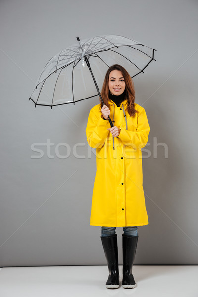 Full length portrait of a pretty girl dressed in raincoat Stock photo © deandrobot