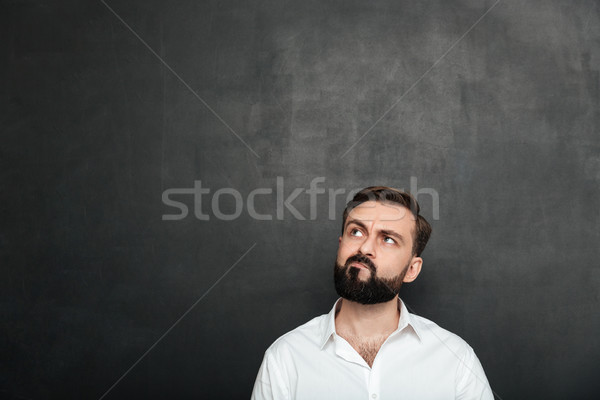 Portrait of brunette serious man in white shirt looking up with  Stock photo © deandrobot