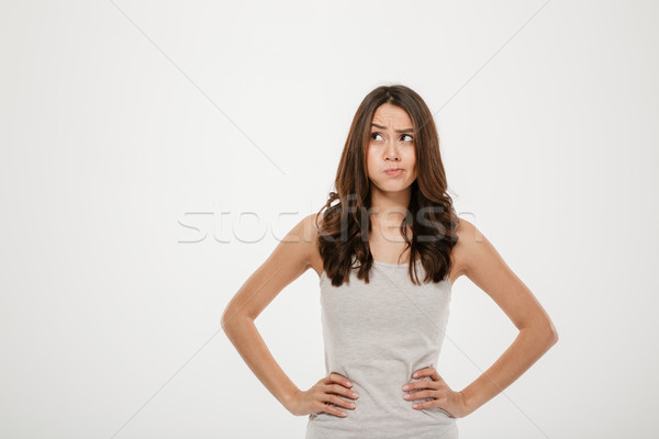 Confused brunette woman with arms on hips looking away Stock photo © deandrobot