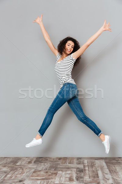 Energetic woman 20s in striped t-shirt and jeans jumping with ha Stock photo © deandrobot