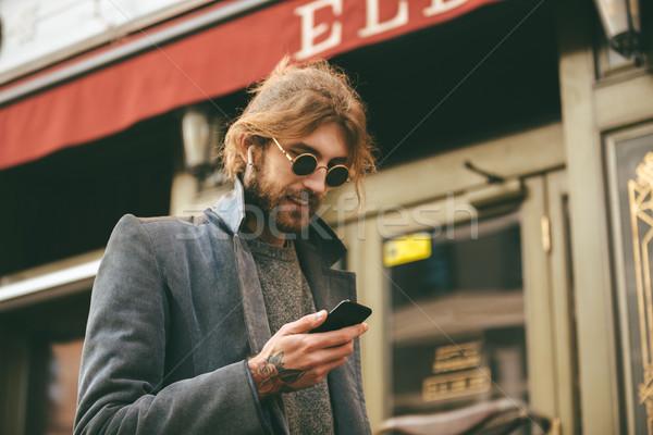 Portrait of an attractive bearded man in earphones Stock photo © deandrobot