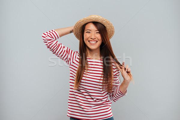 Ridere asian donna maglione Hat guardando Foto d'archivio © deandrobot