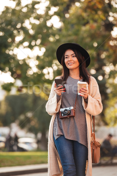 Young smiling asian woman in stylish wear holding smartphone and Stock photo © deandrobot