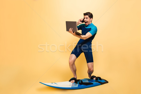 Excited young man on surfing board talking by phone using laptop computer. Stock photo © deandrobot