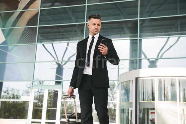 Grave empresario traje caminando maleta fuera Foto stock © deandrobot
