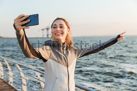 Happy young sportswoman taking selfie with mobile phone Stock photo © deandrobot